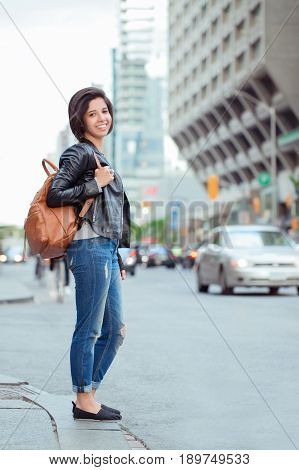 Portrait of smiling laughing beautiful young hispanic latin girl woman with short dark hair in blue jeans and leather biker jacket holding backpack standing in city street ethnic diversity