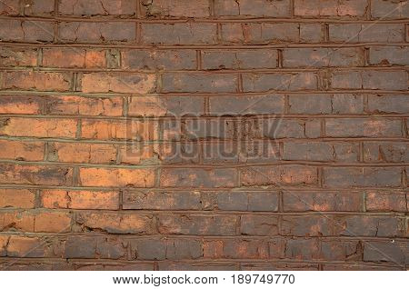 An old grunge brick wall painted with a iron ochre