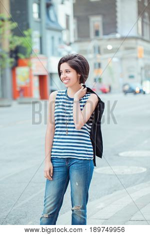 Closeup portrait of beautiful smiling young latin hispanic girl woman with short dark black hair bob outside in busy street with cars natural smile emotion ethnic diversity