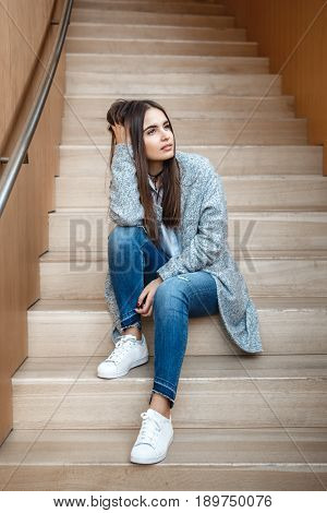 Portrait of pensive Caucasian brunette young beautiful girl woman with long dark hair and brown eyes in white shirt grey coat and blue jeans sitting on staircase looking away