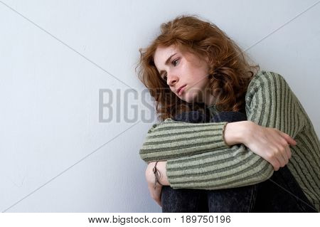A beautiful red-haired girl leaned wearily against the wall and looked sadly away. She clasped her arms