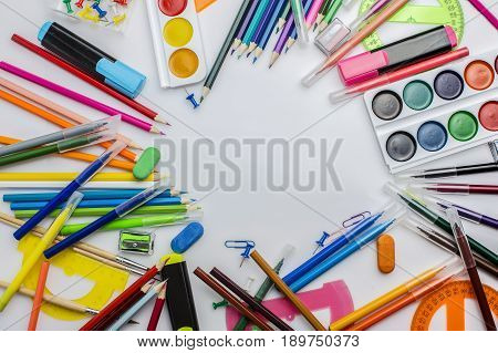 Multicolored stationery on a white table in a light mess. Copy space. Background