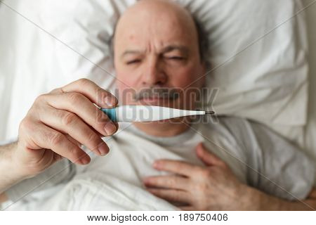 An elderly man measures the temperature with a thermometer. Heat and headache for colds or flu