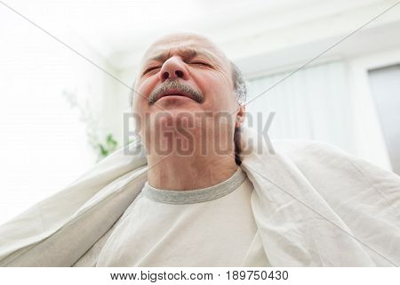 An Elderly Man Is Suffering From Pain And Stress. He Threw A White Blanket Over His Shoulders.