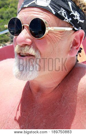 An englishman with a beard wearing a bandana and cool sunglasses while on vacation, 2017