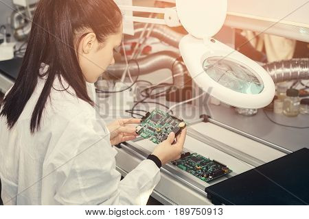 Beautiful female computer expert professional technician examining board computer in a laboratory in a factory. Troubleshooting. Technical support.