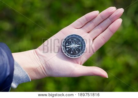 Hand holding the black compass isolated on green background