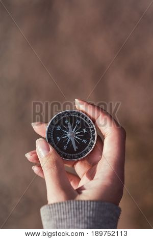 Hand holding the black compass isolated on brown background. Find the right path.