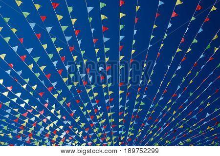 Small triangular waving flags on blue sky