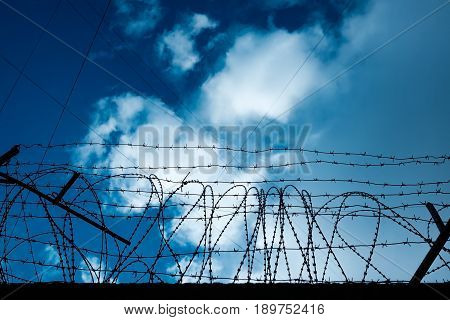 Barbed wire around the perimeter of a prison or secret facility