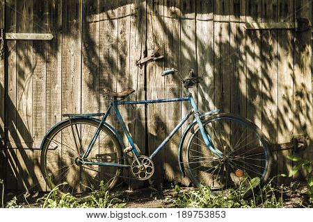 Old blue bicycle on a wooden gate background
