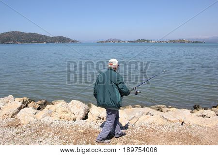 FETHIYE, TURKEY, 31ST MAY 2017: An unknown turkish man fishing in the sea at fethiye in turkey, 31st may 2017