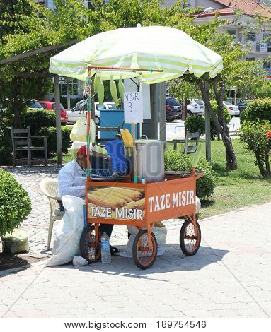 CALIS, TURKEY, 31st may 2017 :  A street vendor selling his fresh corn on the cob from a small cart along the beach at calis in turkey,31st may 2017