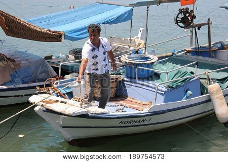 FETHIYE, TURKEY- 31ST MAY 2017: A Turkish fisherman in his small fishing boat in the port of fethiye in turkey , 31st may 2017