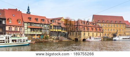Bamberg, Germany - Ferbuary 19, 2017: Bamberg city center panorama with river, half-timbered colorful houses on water and boat