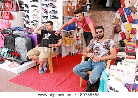 31ST MAY 2017,FETHIYE, TURKEY: Three young turkish men selling fake perfumes and other goods in a local bazaar in fethiye, turkey,31st may 2017
