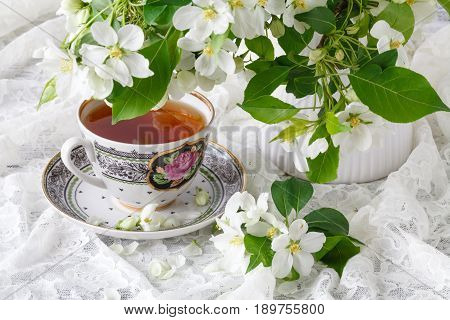 Cup Of Tea On Wooden Table And Apple Blossom. Tea Time Concept. Breakfast Tea Cup Served With Flower