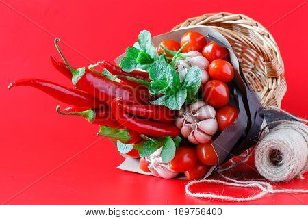 Vegetable edible bouquet of pepper and garlic on red