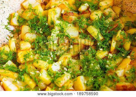 Fried potatoes in a frying pan close up. Kortofel fried in a frying pan and sprinkled with dill and garlic.