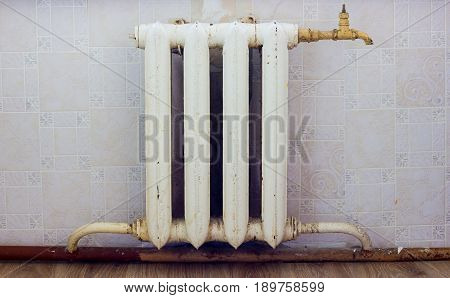 Old cast-iron radiator. In the old room a cast-iron battery of depletion with a wound for draining the water.