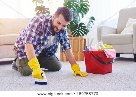 Wide shot of nice male in gloves brushing carpet in spacy room