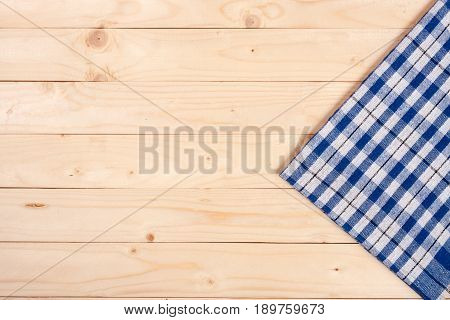 blue checkered tablecloth on a light wooden table with copy space for your text. Top view.