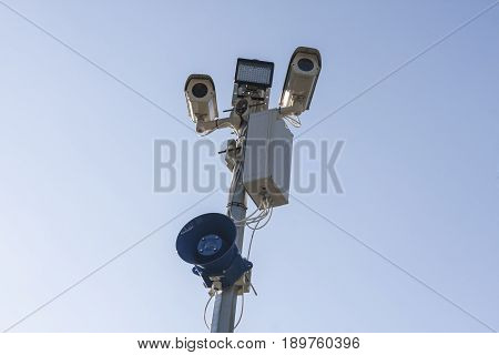Surveillance CCTV security camera on blue sky background with megaphone