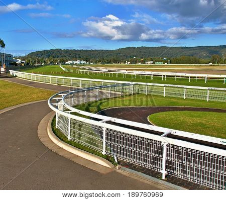 Racecourse image of a country Australian Grass race track with green grass white fences and white cloud in a blue sky. Situated at Gosford New South Wales Australia