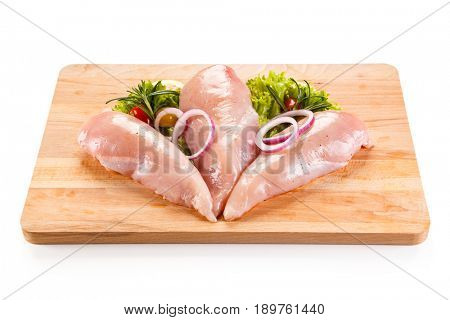 Fresh raw chicken fillets on cutting board on white background