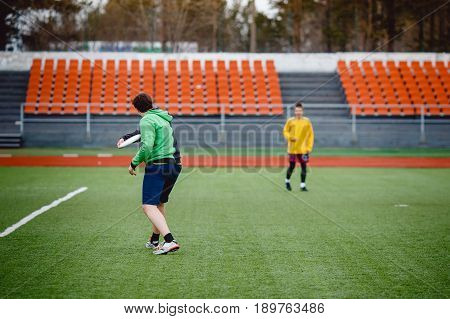 Guy throws throws and catches with flying disk at the sports stadium. Concept is active and mobile in summer. Disk for throwing