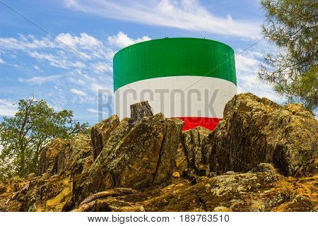 Colors Of Italian Flag On Water Tank Amidst Jagged Rocks