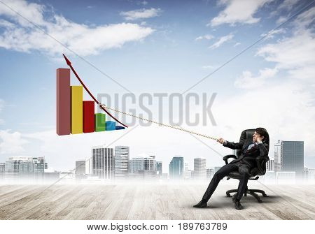 Young businessman outdoors making huge graph move