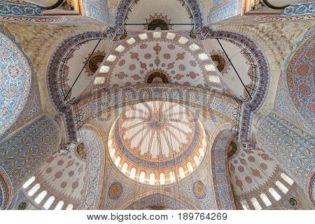 Istanbul, Turkey - April 16, 2017: Decorated ceiling of Sultan Ahmet mosque (blue mosque) with huge pillars domes arches and stained glass windows Istanbul Turkey