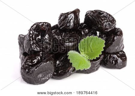 heap of dried plums or prunes with a mint leaf isolated on white background.