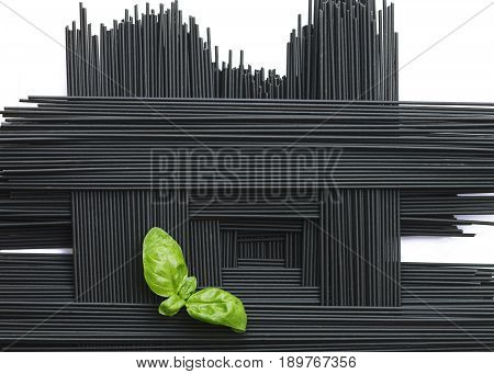 geometric arrangement of black squid ink spaghetti with a green basil garnish on a white background room for copy space