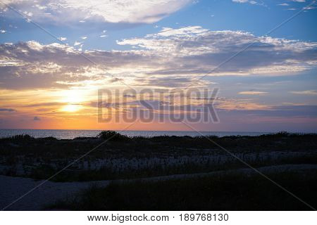 A classic sunset from behind the sand dunes of Venice beach in southwest Florida.