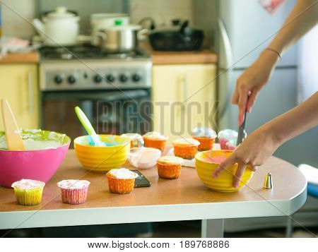 A woman prepares to bake home muffins cupcakes with cream. The concept of homemade baking and hospitality at home Girl cooks goofing around