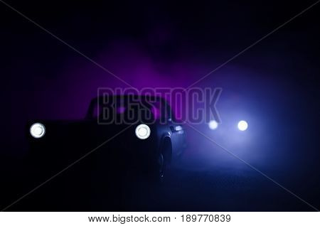 Police Car Chasing A Car At Night With Fog Background. 911 Emergency Response Police Car Speeding To