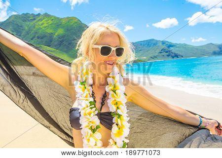 Female enjoying showing her hawaiian lei necklace. Freedom bikini woman in Makua Beach, Waianae coast, Hawaii. On background: Waianae Mountains and Makua Valley, Oahu island. Travel holidays concept.