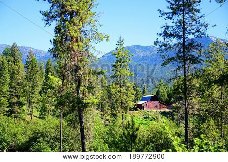 Old red barn nestled in the trees in the Swan Mountain range of Montana