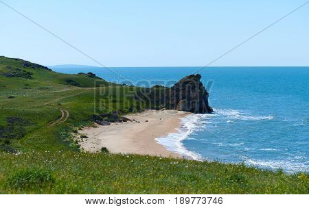 Wild bay with field road. Perfect place for hiking camping to the night. Little waves. Food surfing spot. Background for a extreme sports like windsurfing diving kiting relaxing meditation yoga