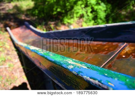 Old metal slide with wooden rails and rust