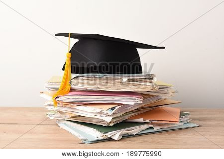 graduation cap with Yellow tassel on stack documents.