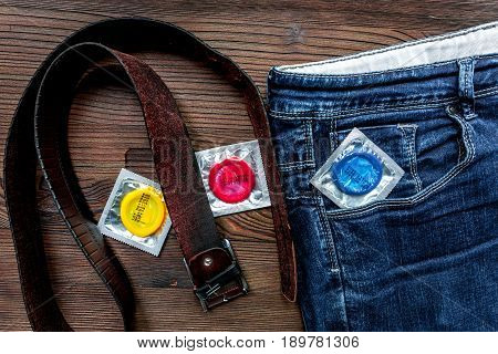 male contraception with condom and jeans on wooden table background top view