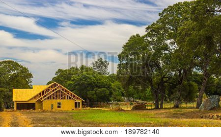 New Home Construction In Open Field With Trees