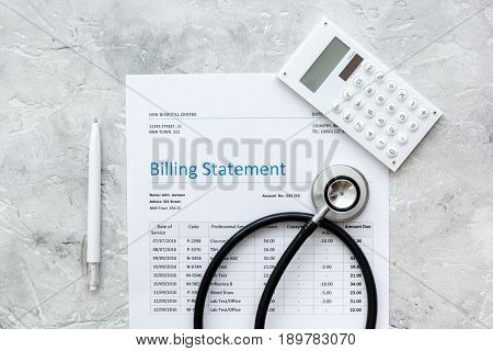 medical treatmant billing statement with stethoscope and calculator on stone desk background top view