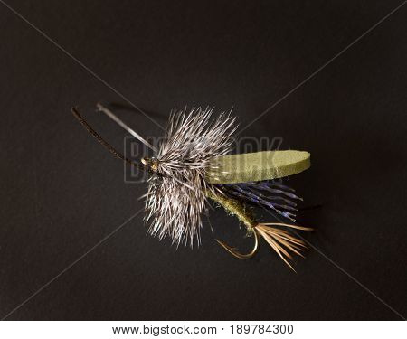 Close up of an olive green foam fly fishing fly with foam wings and iridescent purple threads against a black background.
