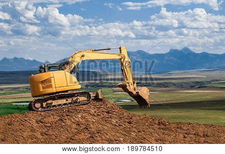 horizontal image of a yellow backhoe working on a big pile of dirt with the scoop open with beautiful blue mountains in the background in the summer time.