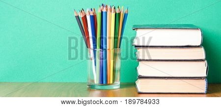 Stack of books and colour pencils on the green background