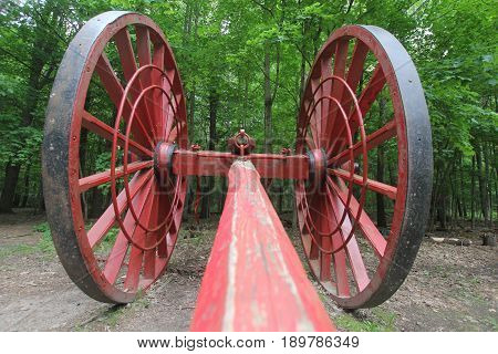 A large Michigan logging wheels sit outside that was once used to move logs out of the forest
